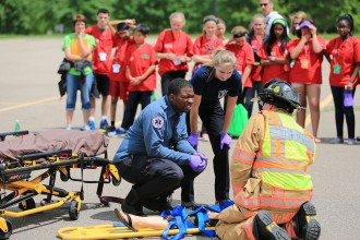 2015 Scrubs Camp participants watch as emergency medical crews demonstrate their response to a car accident.
