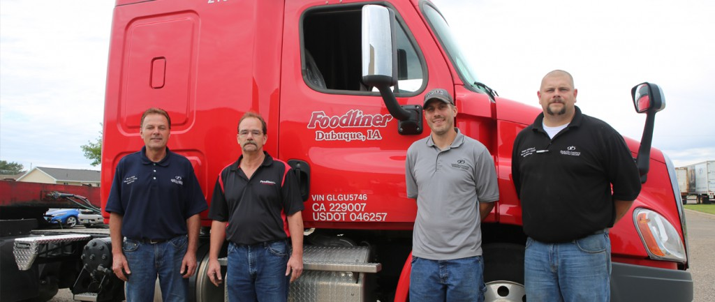 After delivering two donated trucks, Foodliner representative Jeff Larson stands with DCTC faculty Ken Klassen, Jeff Borchardt and Brent Newville.